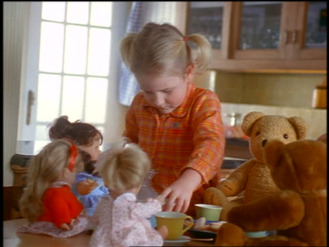 small blonde girl playing with tea cup at tea party with dolls + teddy bears - tea party stock videos and b-roll footage