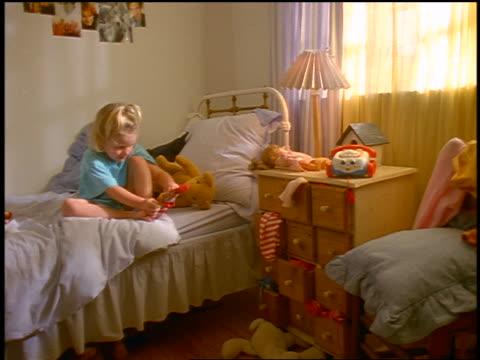 small blonde girl sitting on bed putting on sock - ヘッドボード点の映像素材/bロール