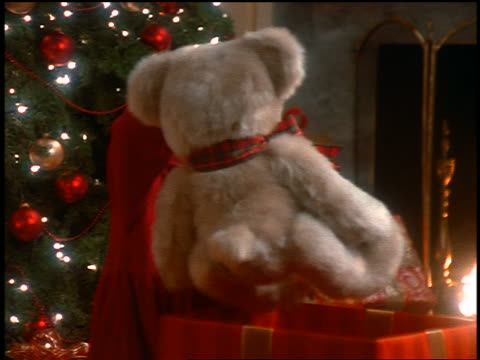 small blonde girl taking stuffed bear from box + hugging it near christmas tree in living room - テディベア点の映像素材/bロール