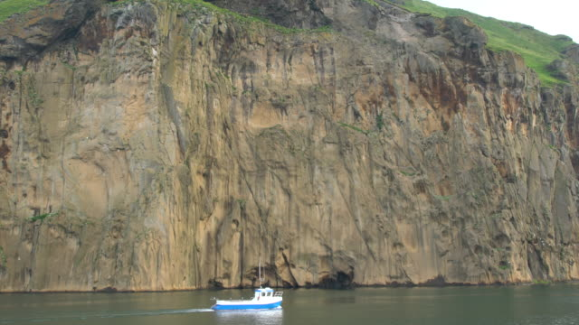 Small blue boat sailing alongside steep cliffs on Heimaey Island, Vestmannaeyjar archipelago, Iceland