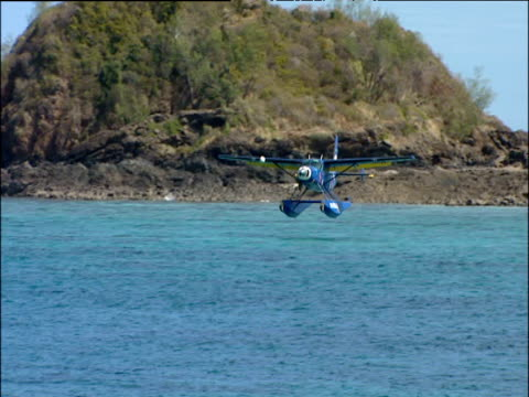 small blue plane comes into land on turquoise sea rocks in background madagascar - splashdown stock videos & royalty-free footage