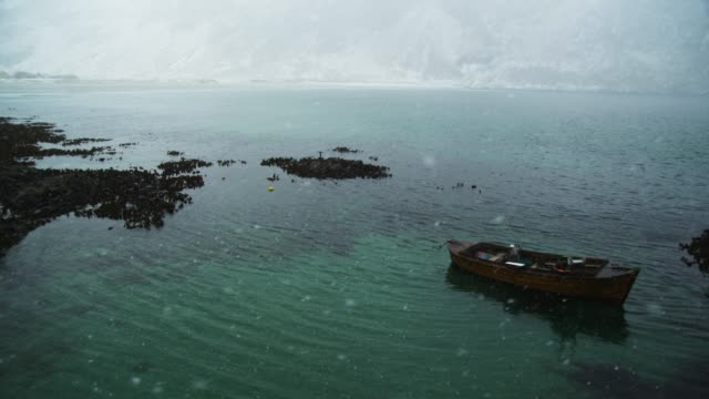 a small boat and falling snow at hoddevik, norway - rowing boat stock videos & royalty-free footage