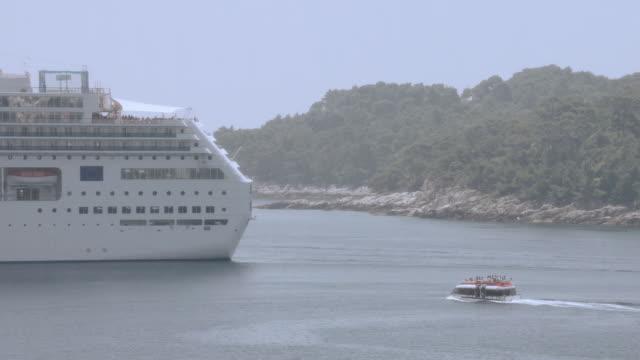 vídeos y material grabado en eventos de stock de ts small boat approaching a cruise liner in a waterway near a hilly coast - pasear en coche sin destino