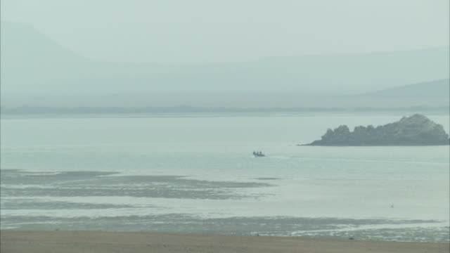 A small boat cruises past a shore where gentle waves wash onto the sand. Available in HD.