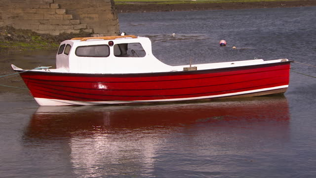 small boat floating in the water - anchored stock videos & royalty-free footage