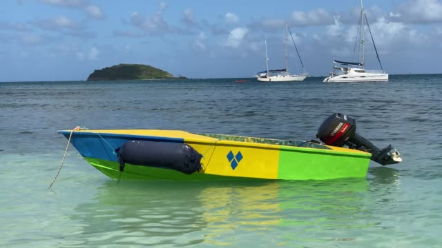 small boat in st. vincent colours bobbing in calm turquoise waters, saltwhistle bay beach, mayreau, grenadines, west indies, caribbean, central america - yacht stock videos & royalty-free footage
