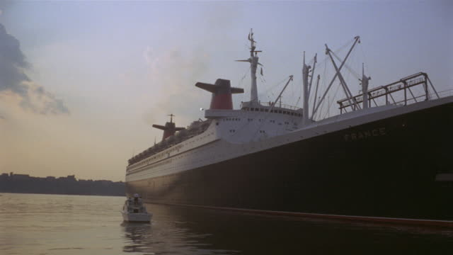 1969 ws small boat moving alongside ocean liner in harbor/ ms sky at dusk/ manhattan, new york, usa - passenger ship stock videos & royalty-free footage