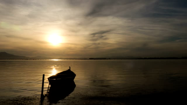 Small boat on lake at sunset.
