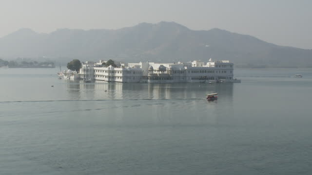A small boat on Lake Pichola glides past the Taj Lake Palace Hotel.