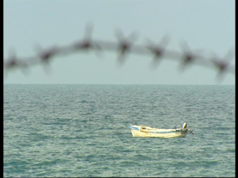 small boat on the sea with rusty barbed wire in the foreground. - civil war stock videos & royalty-free footage