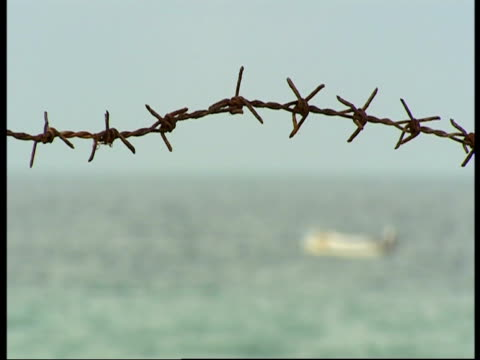 small boat on the sea with rusty barbed wire in the foreground. - sri lanka stock videos & royalty-free footage
