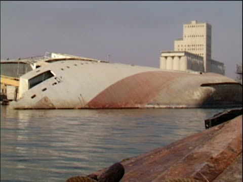 small boat passes sunken gulf war ship rusting in basra harbour iraq - basra video stock e b–roll