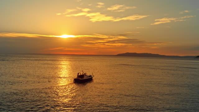 海で夕日に乗って空中の小さなボート - ツレス点の映像素材/bロール