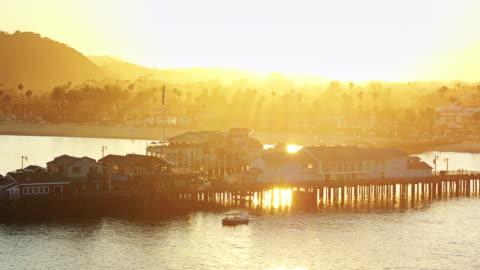 small boat sailing around stearns wharf, santa barbara - drone shot - santa barbara california stock videos & royalty-free footage