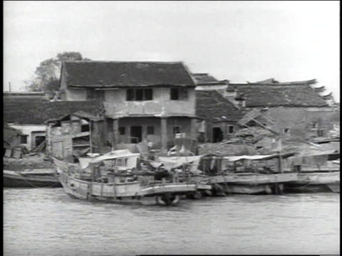 stockvideo's en b-roll-footage met 1938 ws small boats at dock by damaged houses / japan - 1938