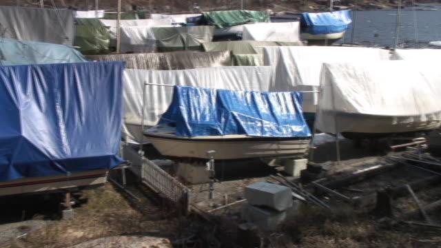 Small boats cowerd under tarpaulin.