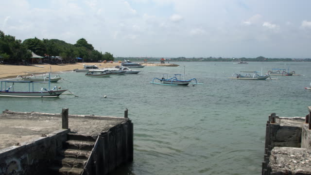 vídeos de stock e filmes b-roll de small boats moored in shallow waters along sanur beach, bali's earliest beach resort - aldeia de pescador