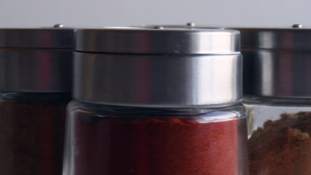 small bottles of kitchen condiments: cumin, ginger, paprika and oregano - condiments stock videos and b-roll footage