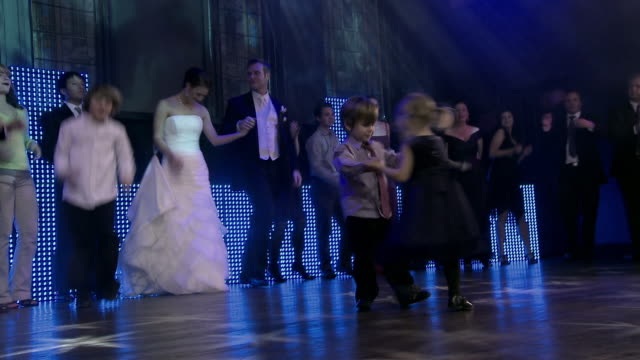 small boy and girl dance together as bride and groom enter to dance