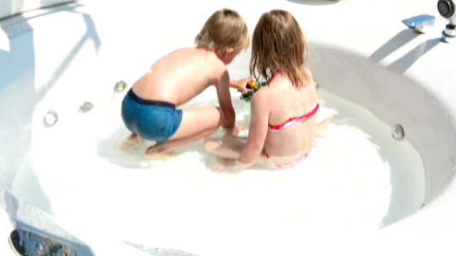 Small boy and girl playing in the pool
