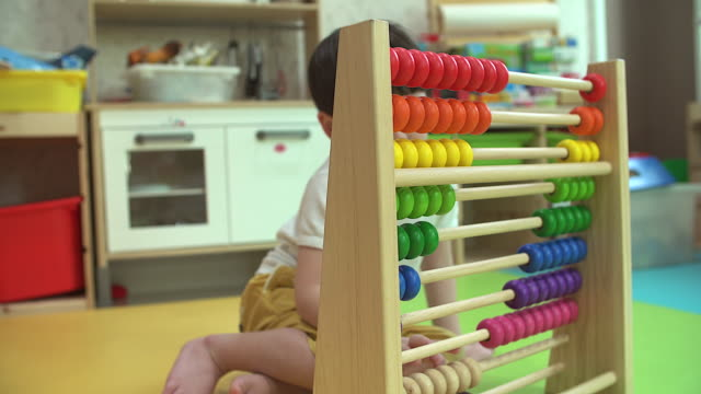Small boy counting with abacus indoor.