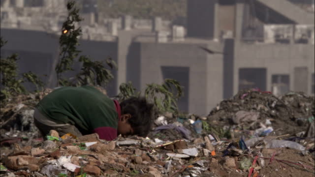 small boy foraging on rubbish tip available in hd. - povertà video stock e b–roll