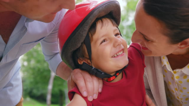 slo mo small boy getting kisses from his mother while wearing a bike helmet - helmet stock videos & royalty-free footage