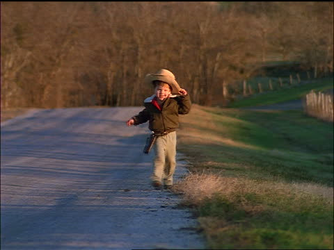 small boy in cowboy hat running on deserted country road towards camera - cowboy hat stock videos & royalty-free footage