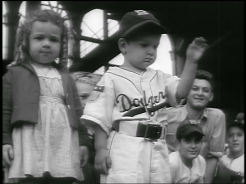 b/w 1947 small boy in dodger uniform little girl standing waving at ebbets field / brooklyn ny - ebbets field video stock e b–roll