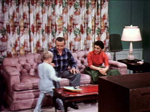 stockvideo's en b-roll-footage met 1957 small boy in pajamas walking to parents sitting on couch in front of television / industrial - voor