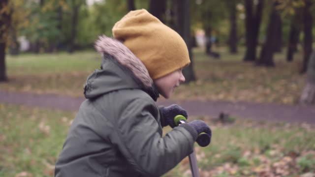small boy in warm clothes riding scooter - dorso umano video stock e b–roll