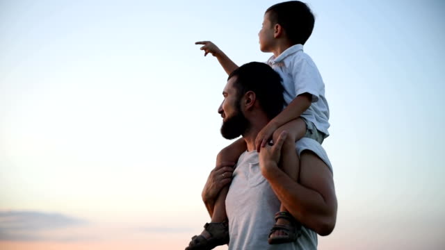 small boy is sitting on his father shoulders and pointing at the sun in the field during beautiful sunset - pointing stock videos & royalty-free footage