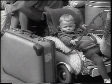 vídeos de stock, filmes e b-roll de b/w 1961 small boy lying in stroller by luggage outdoors / east german refugees berlin wall - fronteira internacional
