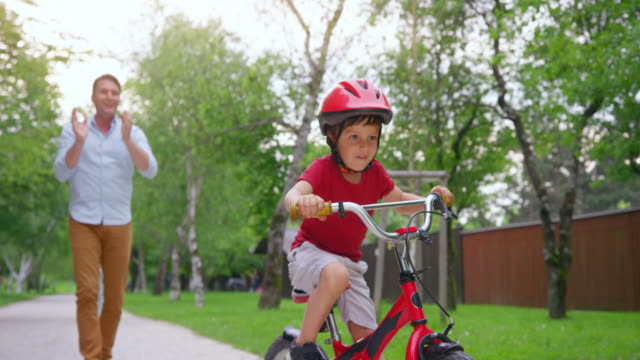 slo mo small boy on his bicycle riding for the first time and father applauding with excitement - tracking shot stock videos & royalty-free footage