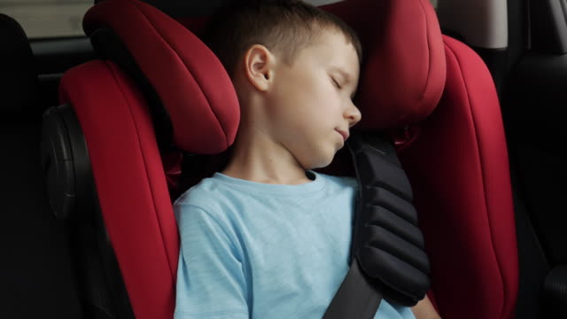 Small boy peacefully sleeping in infant car seat while driving in car