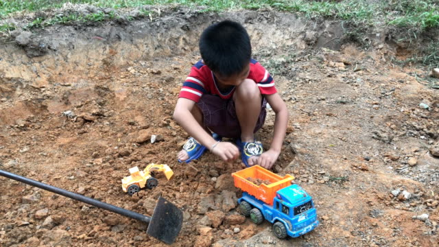 small boy playing his toy plastic dump truck with rocks - bulldozer stock videos and b-roll footage