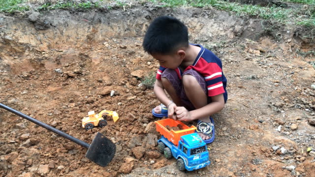 small boy playing his toy plastic dump truck with rocks - dump truck stock videos & royalty-free footage