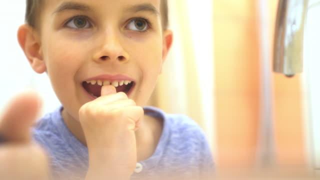 Kleiner Junge seinen Zahn zu ziehen, ob es bereit zu fallen ist