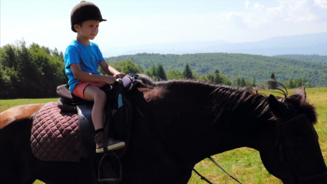 small boy riding a horse in mountains - horseback riding stock videos & royalty-free footage