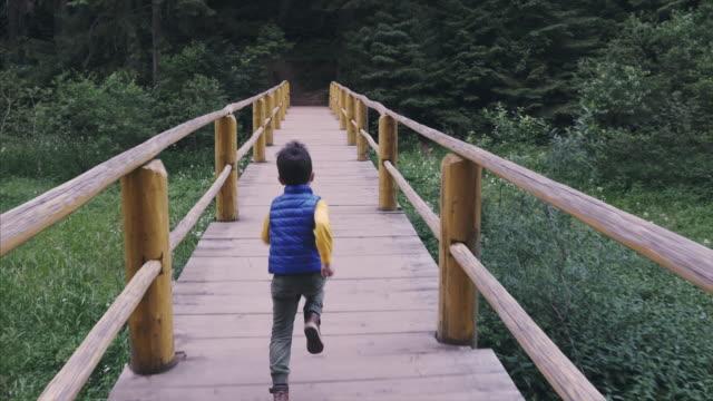 Niño pequeño funcionando a alto ritmo cruzando puente