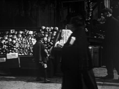 b/w 1913 small boy standing by produce at outdoor market on sidewalk / lower east side, nyc - 1913 stock-videos und b-roll-filmmaterial