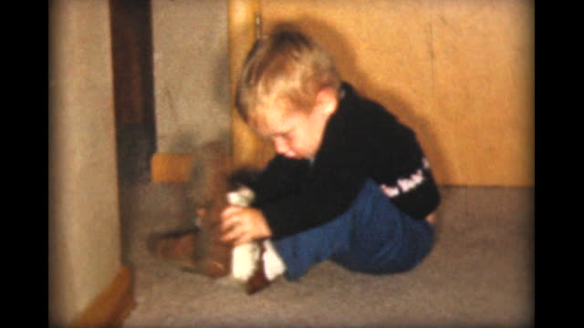 1957 small boy tries to put slippers over his shoes - slipper stock videos and b-roll footage