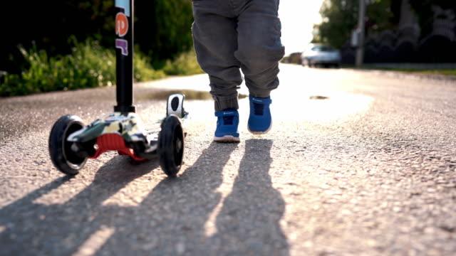 kleiner junge zu fuß und schieben roller - ein männliches baby allein stock-videos und b-roll-filmmaterial