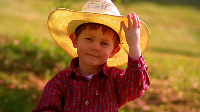 vídeos de stock, filmes e b-roll de ms portrait small boy wearing + tipping straw cowboy hat outdoors - hat