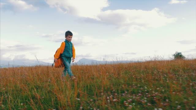 kleiner junge mit schweren rucksack wandern in bergen - schwer stock-videos und b-roll-filmmaterial