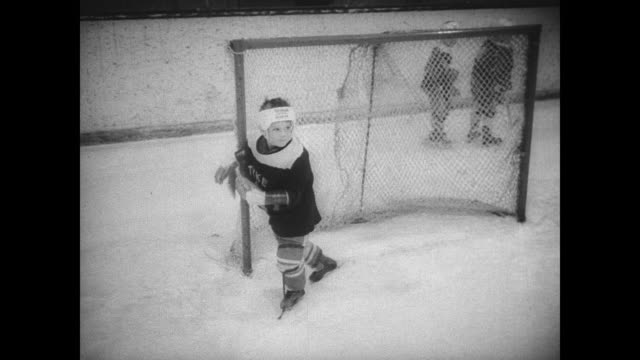 small boys covered in padding holding hockey sticks make their way onto the ice during the canadian pee wee tournament / kids play while falling over... - youth baseball and softball league stock videos and b-roll footage