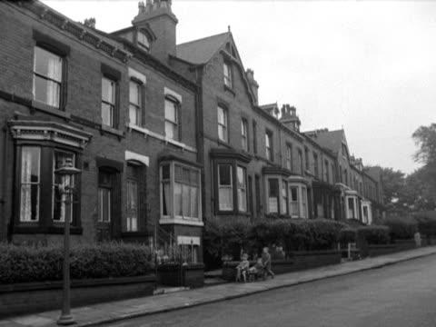Small boys wheel a soap box cart along a quiet terraced street