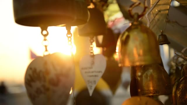 stockvideo's en b-roll-footage met small brass bells written wishes swing in the wind during sunset at wat saket or golden mount - buddhism