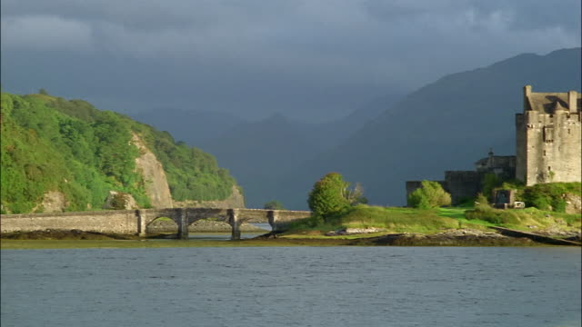 a small bridge crosses to the island of eilean donan castle in scotland. - castle island stock videos & royalty-free footage