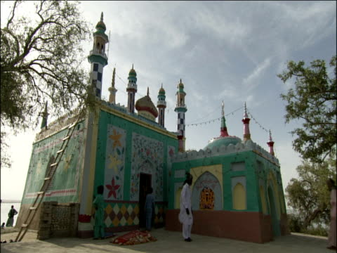 vídeos de stock e filmes b-roll de small brightly painted muslim shrine with people milling about pakistan - paquistão